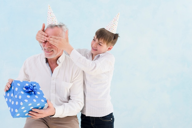 Aanbiddelijke glimlachende jongen die verraste gift geeft aan zijn grootvader door zijn ogen tegen blauwe achtergrond te behandelen