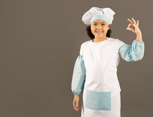 Aanbiddelijke jonge chef-kok die ok teken toont
