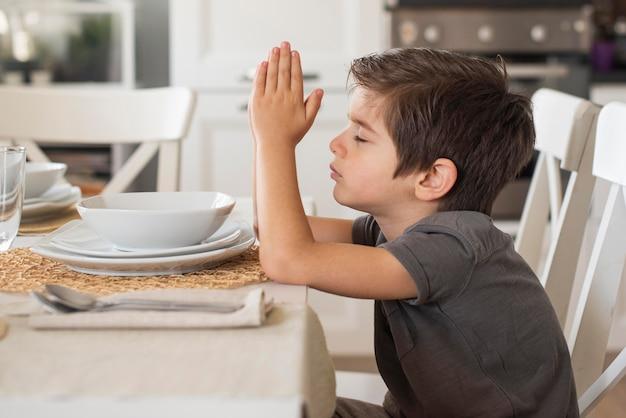 Aanbiddelijke jonge jongen die thuis bidt