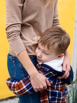Aanbiddelijke jonge jongen die zijn moeder houdt