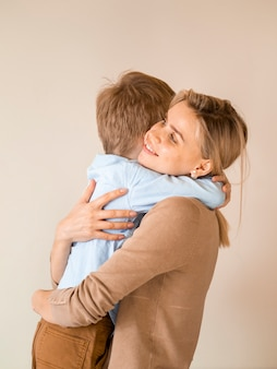 Aanbiddelijke jonge jongen die zijn moeder koestert