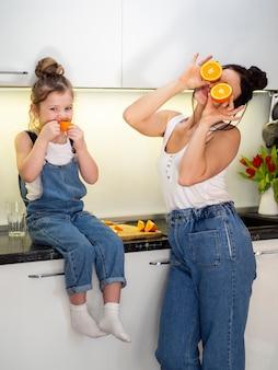 Aanbiddelijke jonge meisje en moeder samen in keuken