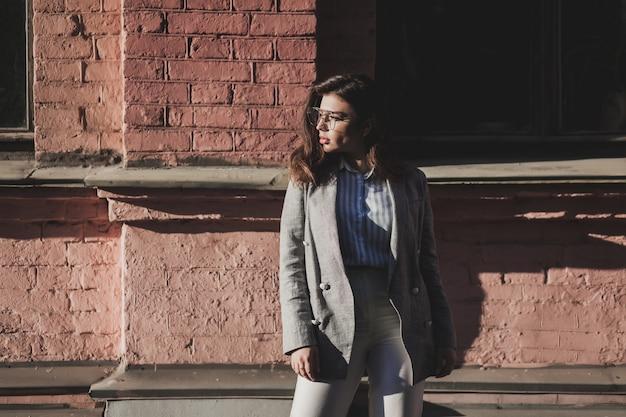 Aanbiddelijke jonge vrouw in jasje en glazen
