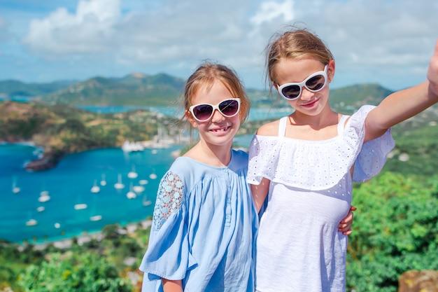 Aanbiddelijke kleine kinderen die van het uitzicht op schilderachtige engelse haven in antigua in caraïbische overzees genieten