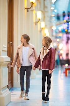 Aanbiddelijke kleine meisjes bij het winkelen in wandelgalerij