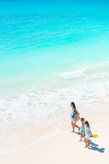 Aanbiddelijke kleine meisjes en jonge moeder op wit strand. uitzicht op de familie en de oceaan van bovenaf