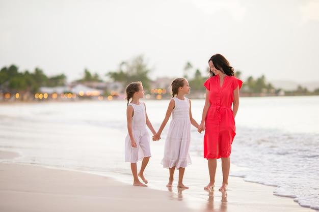 Aanbiddelijke kleine meisjes en jonge moeder op wit strand