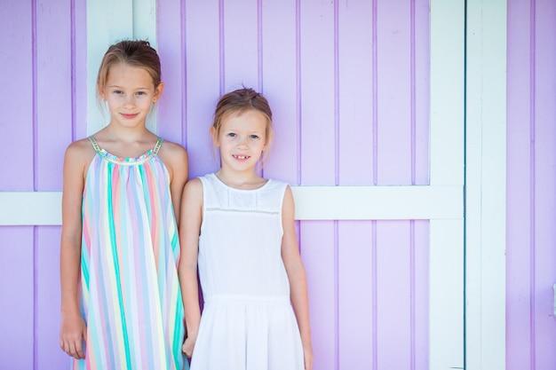 Aanbiddelijke kleine zusters bij strand tijdens de zomervakantie