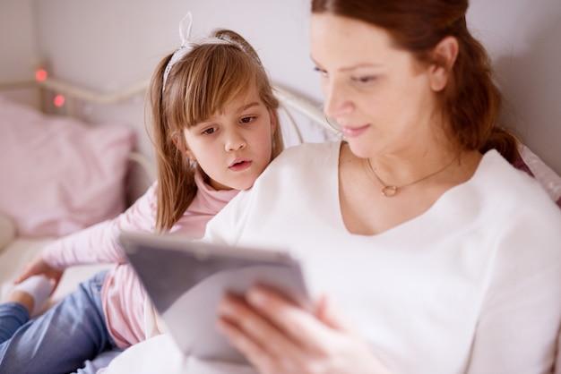 Aanbiddelijke leuke nieuwsgierige meisjespeuter die een hoofd op zwangere moederschouder leunt en een tablet bekijkt.