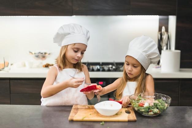 Aanbiddelijke leuke zusters in chef-kokhoed en schorten die voedsel in keuken voorbereiden