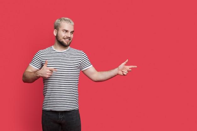 Aanbiddelijke man met baardblond haar wijst naar de vrije ruimte dichtbij hem op een rode studiomuur