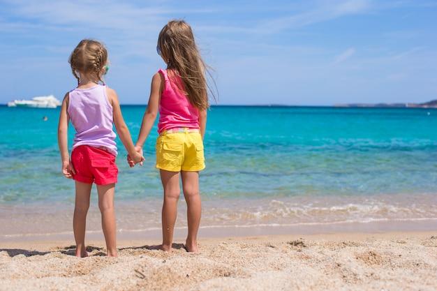 Aanbiddelijke meisjes bij strand tijdens de zomervakantie