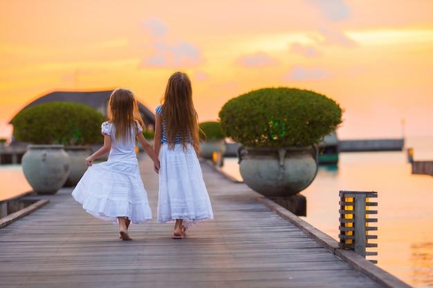 Aanbiddelijke meisjes bij zonsondergang op houten pier