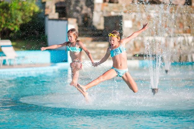Aanbiddelijke meisjes die in openlucht zwembad spelen