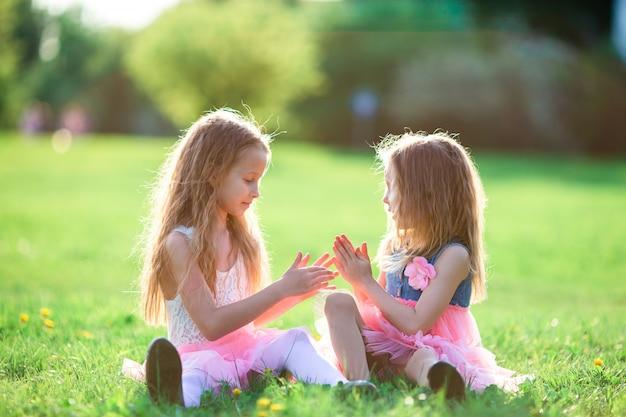 Aanbiddelijke meisjes die op de lentedag in openlucht op het gras zitten