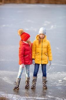 Aanbiddelijke meisjes die op ijsbaan in openlucht in de dag van de de wintersneeuw schaatsen