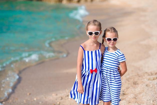 Aanbiddelijke meisjes die pret hebben tijdens strandvakantie