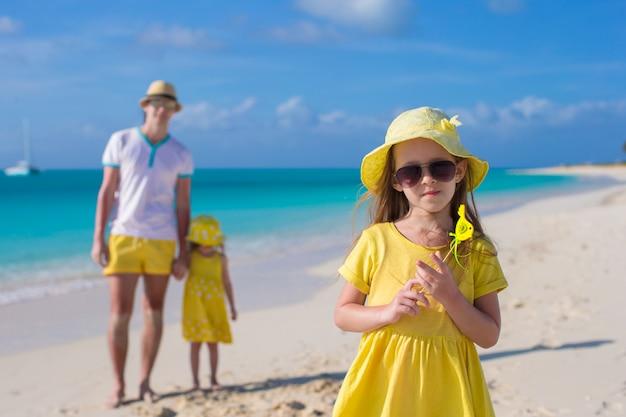 Aanbiddelijke meisjes en gelukkige vader op tropisch wit strand