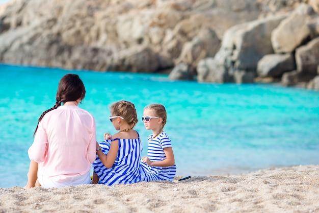 Aanbiddelijke meisjes en jonge moeder op wit strand