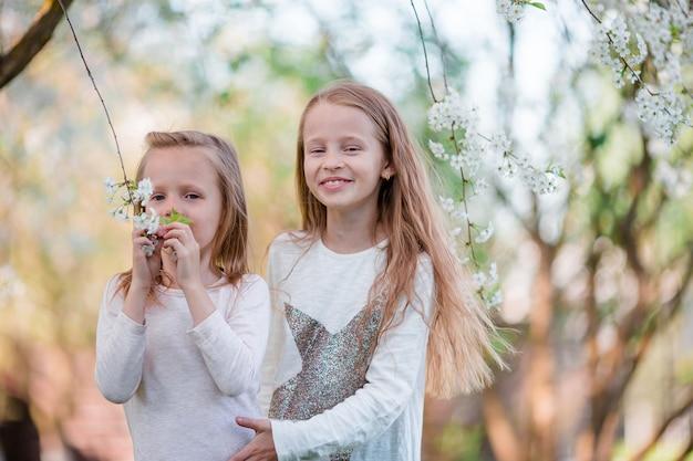 Aanbiddelijke meisjes in de bloeiende tuin van de kersenboom op de lentedag