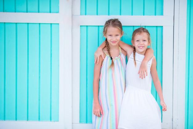 Aanbiddelijke meisjes op van de de zomervakantie traditioneel kleurrijk caraïbisch huis als achtergrond