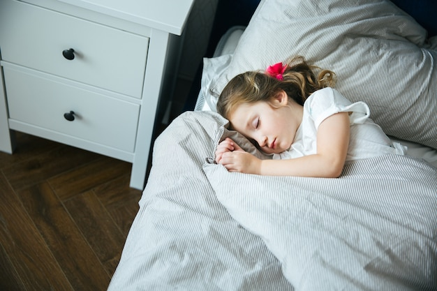 Aanbiddelijke meisjesslaap in het bed in pyjama's onder de thuis deken, kalm en vreedzaam