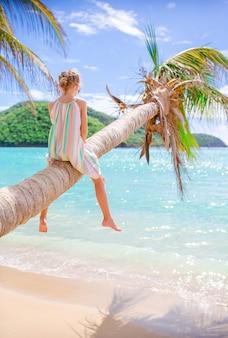 Aanbiddelijke meisjezitting op palm tijdens de zomervakantie op wit strand