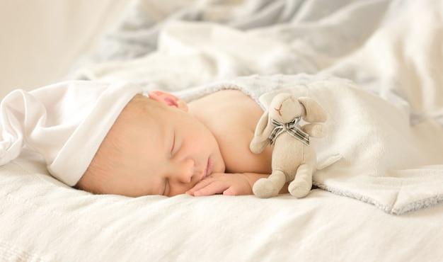 Aanbiddelijke pasgeboren babyslaap in comfortabele ruimte. het leuke gelukkige portret van de zuigelingsbaby met slaperig gezicht in bed