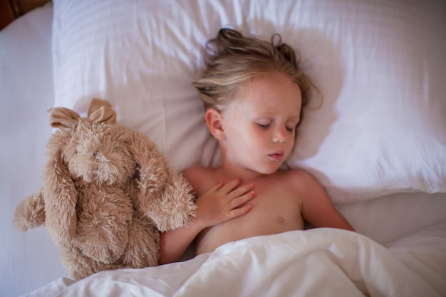 Aanbiddelijke peuter die een dutje met favoriet stuk speelgoed neemt