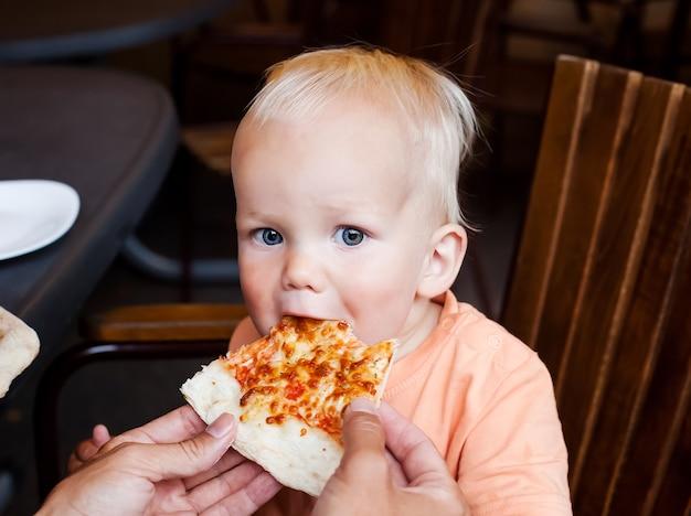 Aanbiddelijke peuterjongen die pizzapunt eet in de zomer van een restaurant kijkend naar de camera
