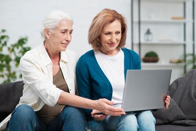 Aanbiddelijke rijpe vrouwen die laptop met behulp van