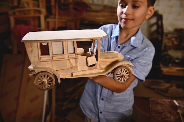 Aanbiddelijke schooljongen die een houten model van met de hand gemaakte auto houdt. timmerwerk, hobby, houtsnijwerk industrie. focus op houten auto