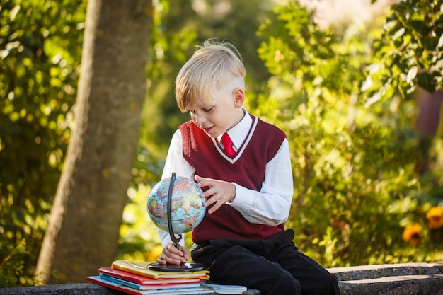 Aanbiddelijke schooljongen met boeken en bol op in openlucht. onderwijs voor kinderen. terug naar school-concept.