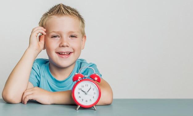 Aanbiddelijke smiley jonge jongen met een klok