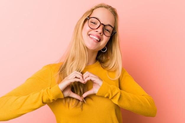 Aanbiddelijke tienervrouw die en een hartvorm met handen glimlachen tonen