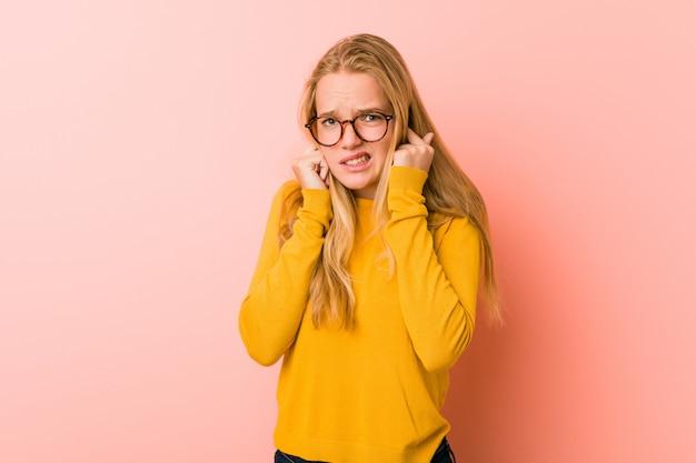 Aanbiddelijke tienervrouw die oren behandelen met handen.