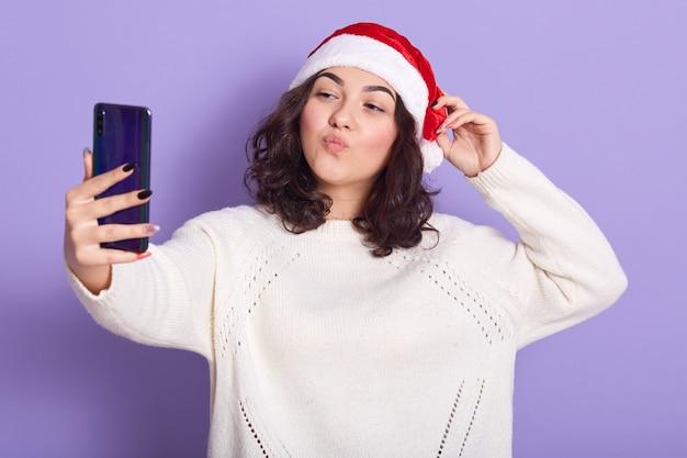 Aanbiddelijke vrij jonge vrouw die één hand op de rode hoed van de kerstman zet