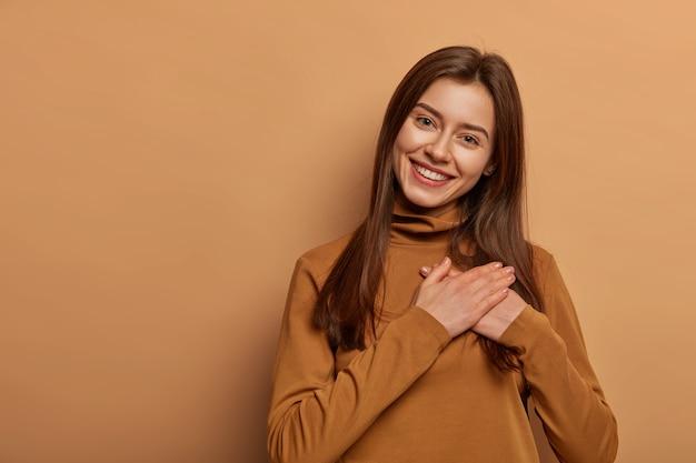 Aanbiddelijke vrolijke vrouw houdt beide handpalmen tegen elkaar gedrukt dichtbij hart in dankbaarheidssymbool