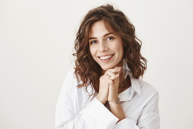 Aanbiddelijke vrouw die en ontroerd of dankbaar glimlacht kijkt