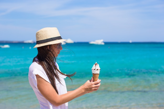 Aanbiddelijke vrouw die roomijs op tropisch strand eet
