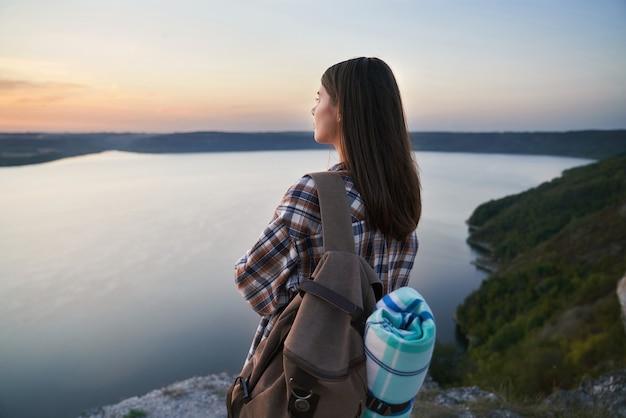 Aanbiddelijke vrouw die van zonsondergang geniet bij bakota-baai