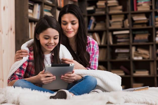 Aanbiddelijke vrouw en jong meisje bij de bibliotheek