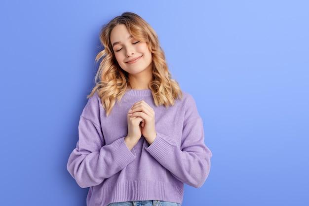 Aanbiddelijke vrouw houdt handen samen staande met gesloten ogen emoties concept