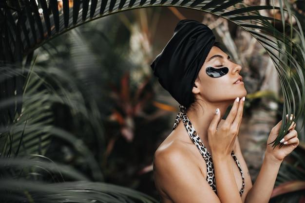Aanbiddelijke vrouw in zwarte tulband die zich op aardachtergrond bevindt. buiten schot van elegante dame met ooglapjes in de buurt van palmbomen.