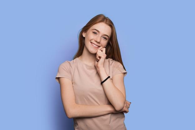Aanbiddelijke vrouw met sproeten met rood haar lacht naar de camera op een blauwe muur