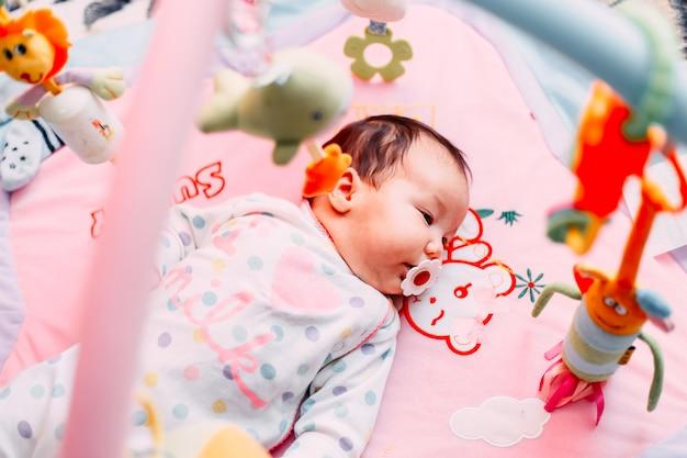 Aanbiddelijke zuigeling die op de kleurrijke mat van het babyspel met speelgoed ligt.