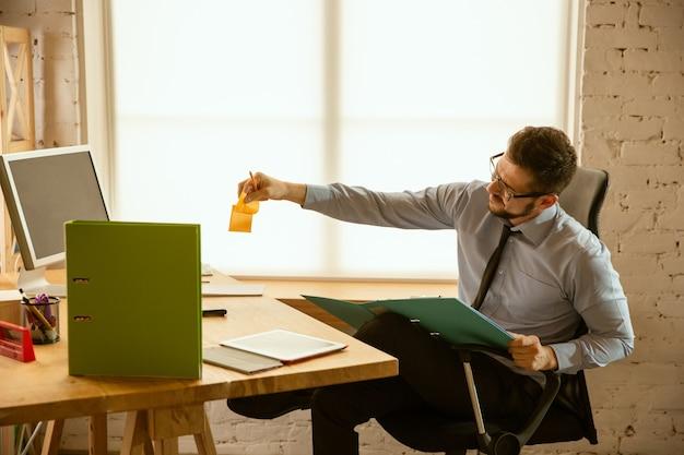 Aanbiedingen. een jonge zakenman die op kantoor werkt en een nieuwe werkplek krijgt. jonge mannelijke kantoormedewerker tijdens het beheren na promotie. ziet er serieus, zelfverzekerd uit. business, lifestyle, nieuw levensconcept.