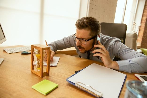 Aanbiedingen. een jonge zakenman die op kantoor werkt en een nieuwe werkplek krijgt. jonge mannelijke kantoormedewerker tijdens het beheren na promotie