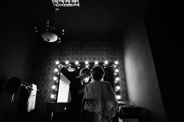 Aanbrengen van een kwast voor het aanbrengen van blush. bruiloft make-up. visagist schildert lippenstiftmeisje. de hand van maakt omhoog kunstenaar in proces binnen. mooi vrouwengezicht met dichte omhooggaand van de avondmake-up