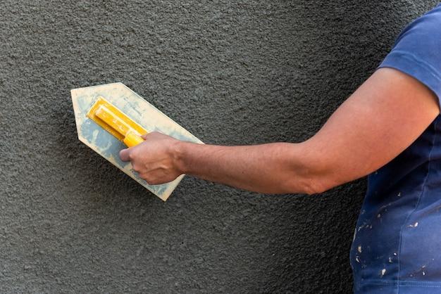 Aanbrengen van sierpleister op muur met bouwgereedschap.